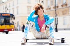 Femme géniale s'asseyant sur la planche à roulettes Photographie stock libre de droits