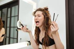 Femme gênée triste avec des brosses et cosmetisc pleurant dans la salle de bains Image stock