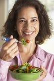 Femme âgé moyen mangeant d'une salade Images libres de droits