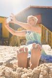 Femme gaie à l'aide du téléphone intelligent tout en se reposant sur le sable Photos stock