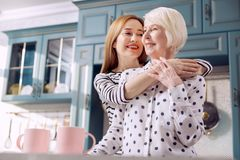 Femme gaie étreignant sa mère supérieure près du comptoir de cuisine Images stock