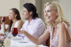 Femme gaie appréciant le dîner avec des amis Photos stock