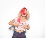 Femme gaie avec des couleurs rouges sur le visage Image stock
