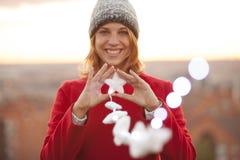Femme gaie avec le chapeau tenant la décoration de Noël des étoiles IL Images stock
