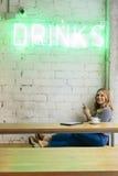 Femme gaie ayant une boisson dans le cafétéria moderne Images libres de droits