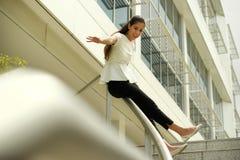 Femme gaie d'affaires allant glisser en bas sur le rail pour la joie Image libre de droits