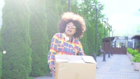 Femme gaie d'afro-américain avec une coiffure Afro avec la boîte MOIS lent clips vidéos
