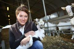 Femme gaie d'agriculteur avec des chèvres dans la grange Image libre de droits
