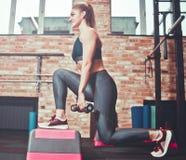 Femme gaie d'athlète faisant des mouvements brusques avec des haltères photos libres de droits