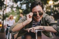Femme gaie dans des lunettes de soleil avec le vélo Photos stock