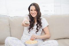 Femme gaie dans des pyjamas ayant le maïs éclaté tout en regardant la TV Image libre de droits