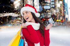 Femme gaie dans le costume de Santa tenant le panier et la carte de crédit Photos libres de droits
