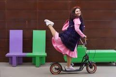 Femme gaie dans une robe rose et un cap pourpre de fourrure montant un scooter image stock