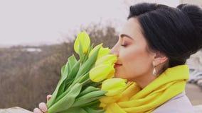 Femme gaie de brune appréciant l'odeur des tulipes jaunes données par l'homme aimé banque de vidéos