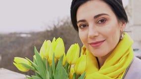 Femme gaie de brune appréciant l'odeur des tulipes jaunes données par l'homme aimé clips vidéos