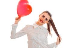 Femme gaie de brune dans l'amour posant avec le baloon rouge de coeur dans des ses mains d'isolement sur le fond blanc Images libres de droits