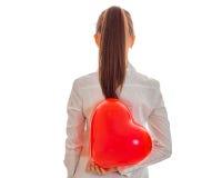 Femme gaie de brune dans l'amour posant par derrière avec le baloon rouge de coeur dans des ses mains d'isolement sur le fond bla Photo stock