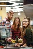 Femme gaie de caissier sur l'espace de travail dans le supermarché Image libre de droits