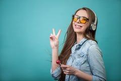 Femme gaie de hippie avec les écouteurs et la sucrerie Photographie stock