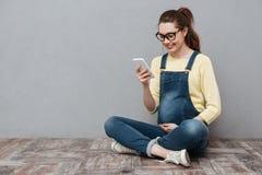 Femme gaie enceinte à l'aide du téléphone portable Photographie stock