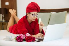 Femme gaie faisant des emplettes en ligne avec la carte de crédit et l'ordinateur portable sur un lit photos stock