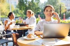 Femme gaie faisant un appel tout en se reposant sur la terrasse de restaurant Image libre de droits
