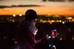 Femme gaie faisant un souhait tenant une bougie de Noël la nuit Images stock