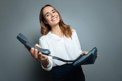 Femme gaie heureuse tenant un téléphone attaché Photos stock