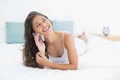 Femme gaie à l'aide du téléphone portable dans le lit Photographie stock