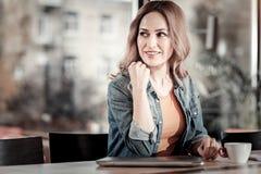 Femme gaie mignonne examinant la distance tout en étant dans un café Image stock