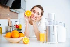 Femme gaie montrant la moitié de la séance orange sur la cuisine Image libre de droits