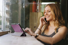 Femme gaie parlant à son téléphone portable et employant la technologie moderne Photos stock