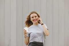 Femme gaie parlant à son téléphone tout en buvant du café Photographie stock