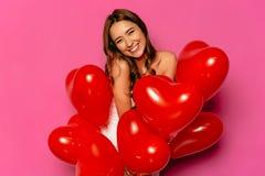 Femme gaie posant à l'appareil-photo avec les ballons rouges photographie stock libre de droits