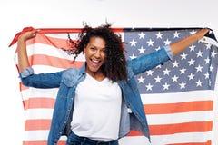 Femme gaie posant avec un drapeau américain Photo stock