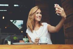 Femme gaie posant tout en se photographiant pour la photo sociale de réseau, l'espace de copie photographie stock