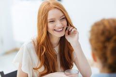 Femme gaie s'asseyant et riant avec son ami en café Photographie stock libre de droits