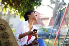 Femme gaie s'asseyant sur un banc de parc avec un téléphone portable Photos libres de droits