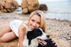Femme gaie se trouvant et embrassant son chien sur la plage Photos libres de droits