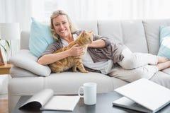 Femme gaie se trouvant sur le sofa caressant un chat de gingembre photographie stock