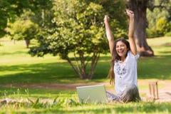 Femme gaie soulevant des mains avec l'ordinateur portable en parc Image libre de droits
