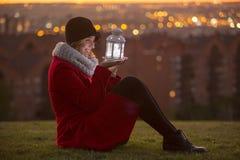 Femme gaie sur un manteau rouge d'hiver tenant une lanterne menée de lumières Photo stock
