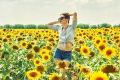 Femme gaie sur une promenade d'été dans le domaine avec des tournesols images stock