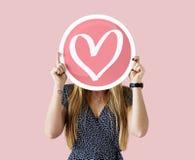 Femme gaie tenant l'icône de coeur Photos libres de droits