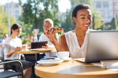 Femme gaie tenant le croissant et lisant de l'ordinateur portable Images libres de droits