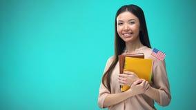 Femme gaie tenant le livre de drapeau des Etats-Unis, éducation à l'étranger, apprenant la langue banque de vidéos