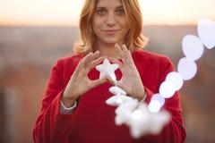 Femme gaie tenant une étoile de Noël avec l'illumination magique Photographie stock libre de droits