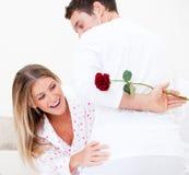 Femme gaie trouvant un bahind de rose son mari photo stock