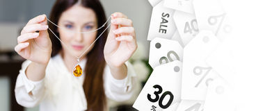 Femme gardant le collier avec le saphir jaune, vente des bijoux Photos libres de droits