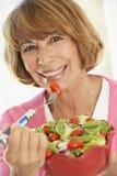 Femme âgée moyenne mangeant d'une salade verte fraîche Photo stock